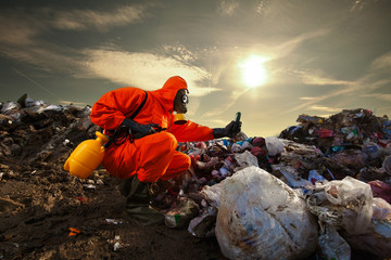 Sanitation worker measuring pollution on the landfill