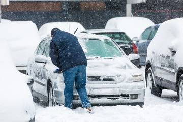 Man scraping frozen snow from the car windows during snowfall
