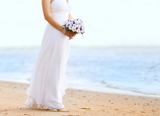 Beautiful bride with wedding bouquet outdoors on the coast sea