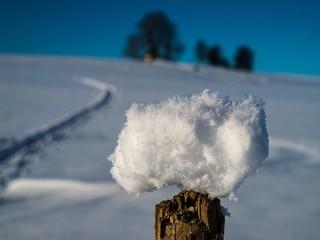 Schneeball vor idyllischer Winterlandschaft