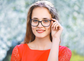 Portrait pretty girl in glasses outdoors in spring day