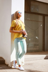 Street fashion, stylish pretty woman in sunglasses with retro vi
