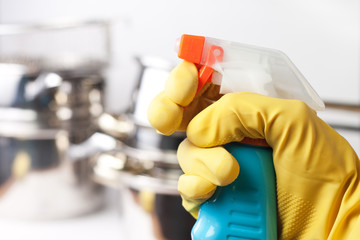 hand in protective glove holding spray. cleaning a kitchen conce