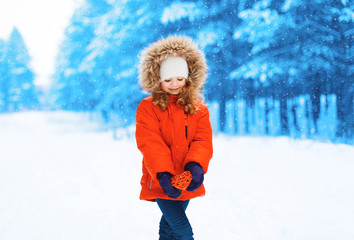 Little girl child with heart in hands outdoors winter