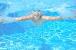 Kid swims in pool underwater, girl swimming and having fun