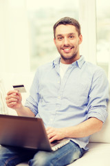 smiling man working with laptop and credit card