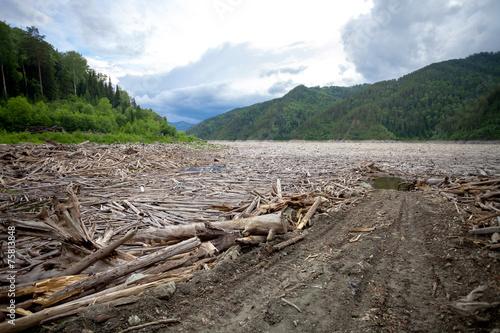 Leinwandbild Motiv Driftwood near dam of hydro power plant with access road