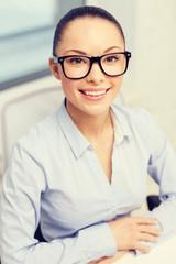smiling businesswoman in eyeglasses in office