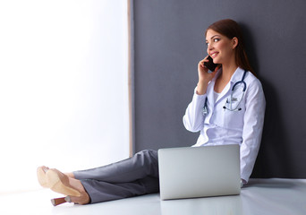 Doctor sitting  the floor near wall  with laptop and talking on