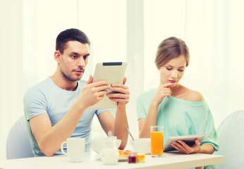 concentrated couple with tablet pc reading news