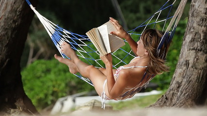 Young lady reading a book in a swinging hammock in a garden