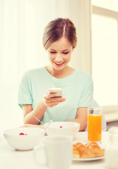 smiling young woman with smartphone reading news