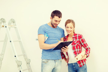 smiling couple with clipboard and wallpaper roll
