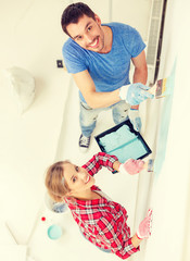 smiling couple painting wall at home