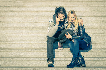 Beautiful hipster couple in love having a smartphone call