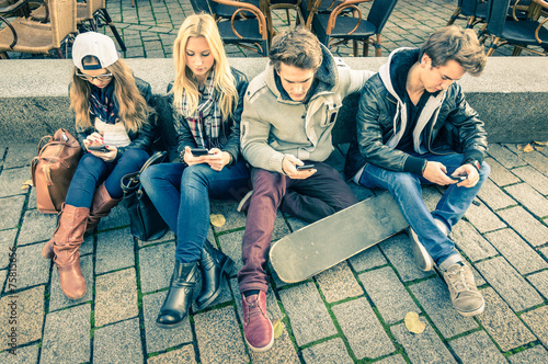 Leinwandbild Motiv Group of young hipster friends playing with smartphone