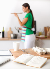 Young woman in the kitchen, standing near desk