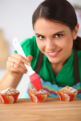 Young woman is making cakes in the kitchen