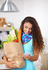 Smiling woman with mobile phone holding shopping bag in kitchen