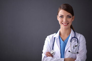 Doctor woman with stethoscope standing near grey wall