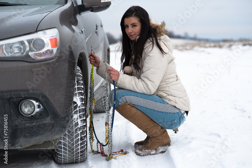 Woman Putting Snow Chains Onto Tyre Of Car - 75816455