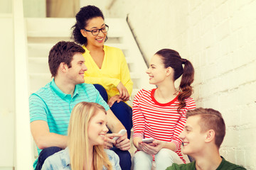 smiling students with smartphone having discussion