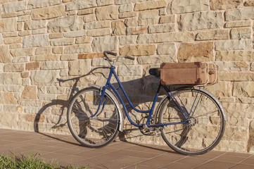 Vintage bicycle and old suitcase in a stone wall
