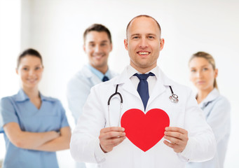 smiling male doctor with red heart and stethoscope