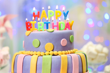 Delicious birthday cake on shiny light background