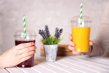Two female hands with fast food cups of juice at wooden table