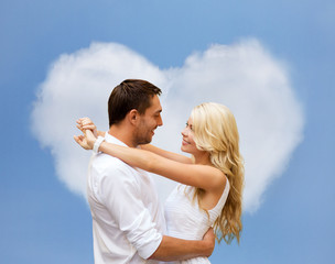 happy couple hugging over heart shaped cloud