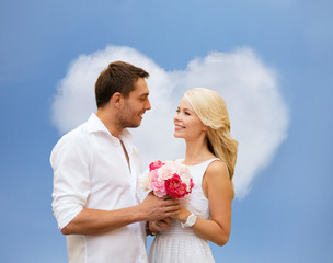 happy couple with flowers over heart shaped cloud