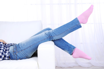 Female legs on sofa close-up