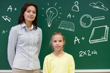 little school girl with teacher at blackboard