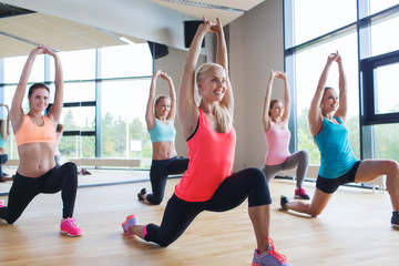 group of women making lunge exercise in gym