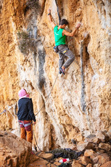 Young man lead climbing on cliff, female climber belaying