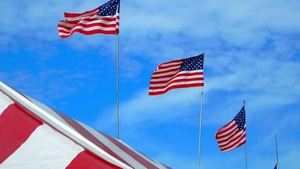 american flags high in blue sky