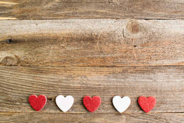 Four glitter hearts on reclaimed wood, valentines day background