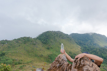Hand with drink water are climbing limestone mountains