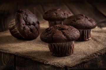 Chocolate cake muffins on a table. Dark lighting