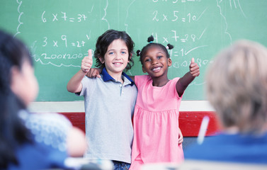 Caucasian kid and afro american female smiling to the classroom