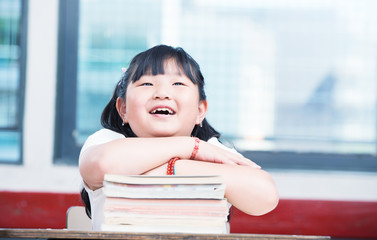 Portrait of cute asian girl on top of book stack looking upwards
