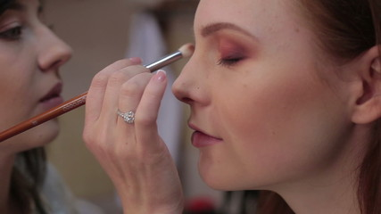 Visagiste makes makeup for  model, professional makeup