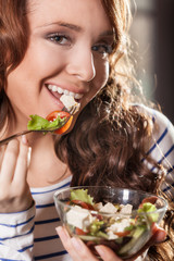 Young woman eating fresh vegetable salad