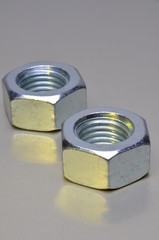 Two steel nuts with yellow light reflection