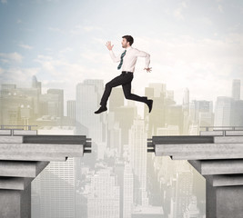 Energetic business man jumping over a bridge with gap