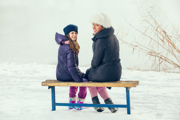 Young mother with her daughter sitting on wooden bench in park