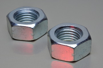 Two steel nuts with red light reflection