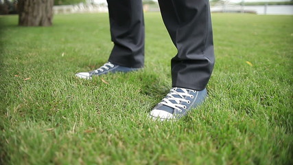 close up, the feet  in sneakers stand down on the grass