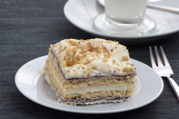 Piece of layered cake on white plate.